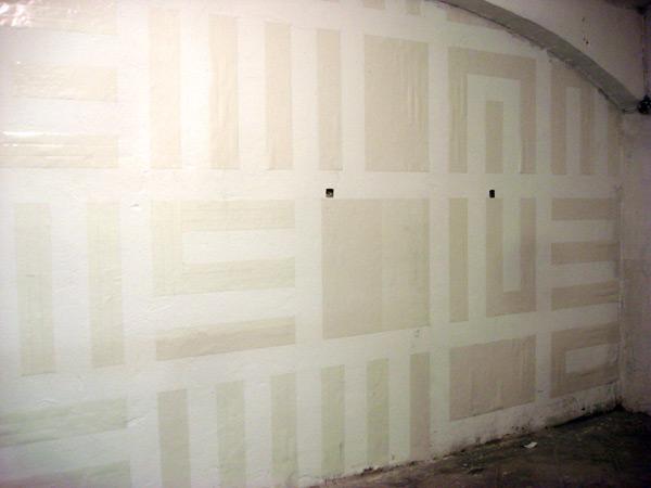 ...con cinta doble cara en una pared grande de la galería...