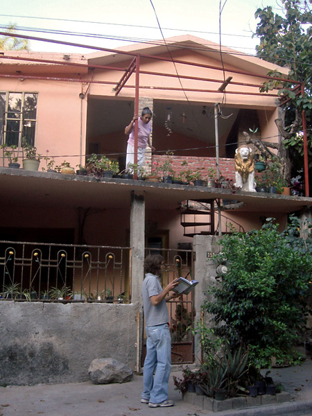 Luis preguntando a los vecinos para pintar sus paredes y enseñando el libro del proyecto